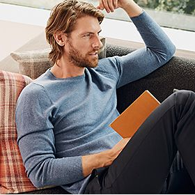 Man wearing blue cashmere jumper and navy wool trousers