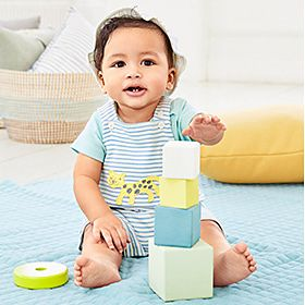 Baby boy playing with building blocks wearing a green bodysuit and blue and white striped romper