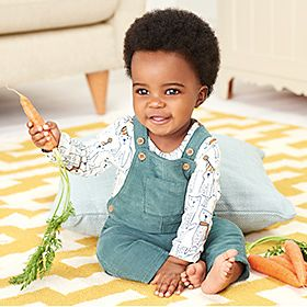 Baby girl in dungarees and long-sleeve bodysuit