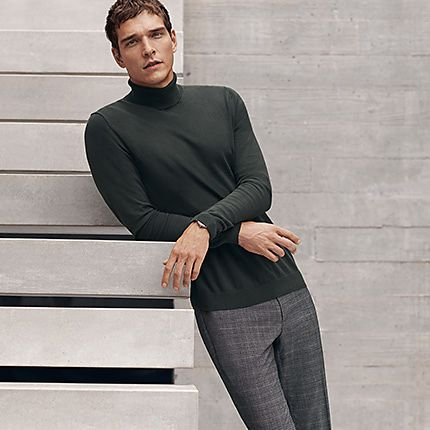 Man wearing roll-neck jumper and smart trousers