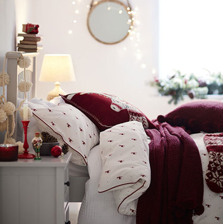 Red and white Christmas bedding on wooden bed
