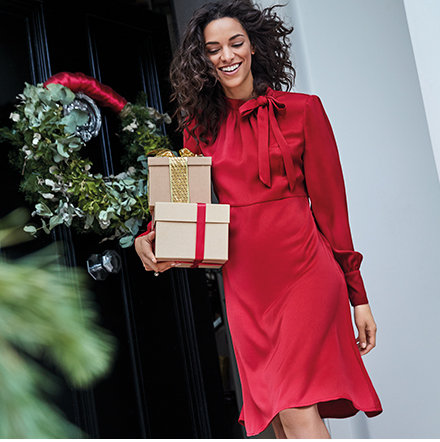Model by a front door wearing a red silk dress carrying Christmas gifts