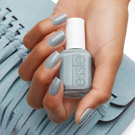 A bottle of Essie nail polish held in a ladies hand