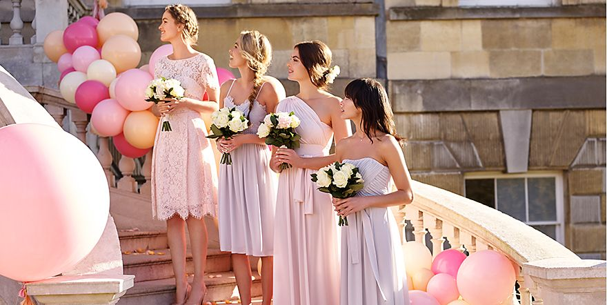 Four bridesmaids holding bouquets on a staircase