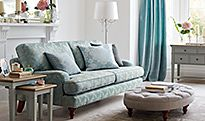 Sage green sofa in living room with ottoman