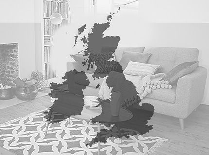 A sofa, rug and cushions with a map of the UK and Ireland