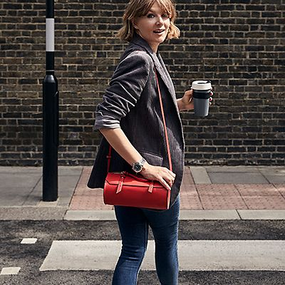 Alexandra Fullerton wearing a grey jacket, red cross-body bag and blue skinny jeans