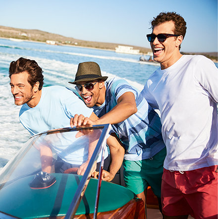 Three men on a speed boat wearing mens summer clothing