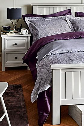 A white bed with grey bedding