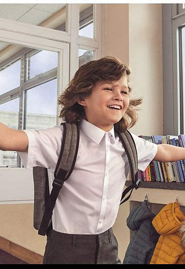 Boy wearing white short-sleeved easy-iron M&S school shirt