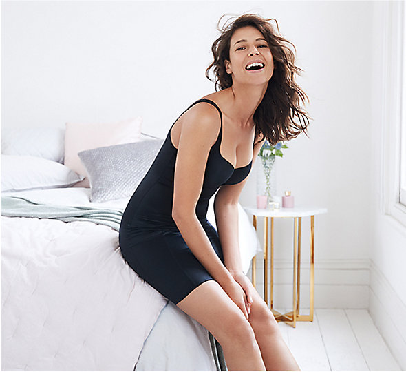 Woman sitting on a bed laughing wearing black shapewear