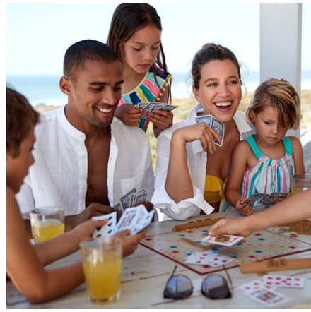 Family by the sea playing cards wearing M&S holiday clothing