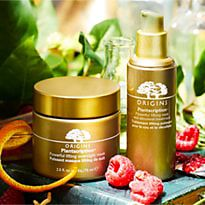 Origins Plantscription skin care surrounded by raspberries and orange peel