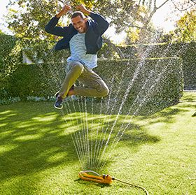 Man wearing chinos jumping through a sprinkler