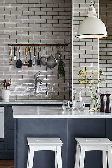 modern kitchen with white tiles, a marble worktop and white stools