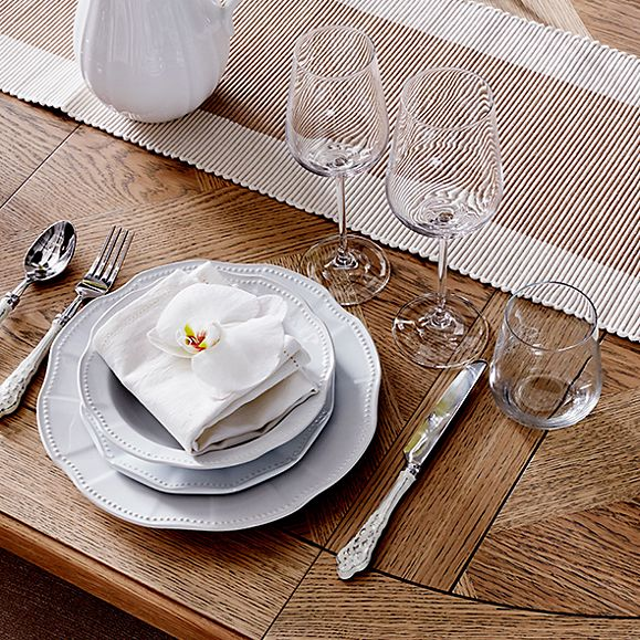 An oak dining table with crockery and glasses