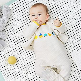 Baby lying on bed wearing all-in-one
