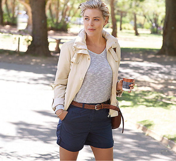 Woman in cream jacket and blue shorts