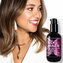 Smiley woman next to a bottle of Bumble and bumble Save the Day Daytime Repair Fluid