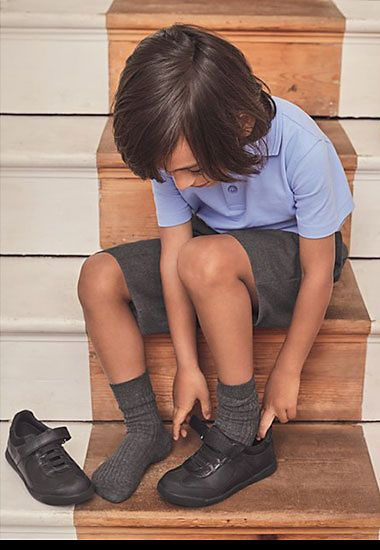 Boy in blue school shirt and grey school shorts putting black leather shoes on