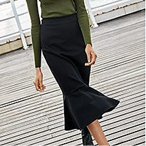 Woman on pier wearing a green jumper and black midi skirt