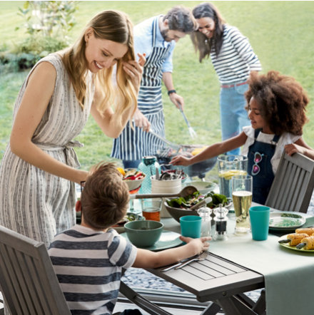 Family and friends having a barbecue with garden furniture and picnicware