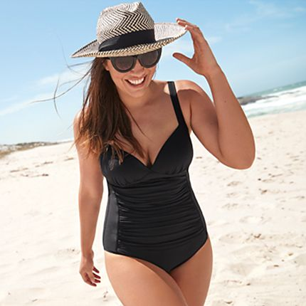Woman walking on a sandy beach wearing a black swimsuit, sun hat and sunglasses