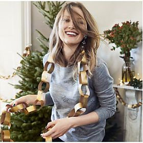 Model next to a Christmas tree wearing grey jumper and gold paper chain