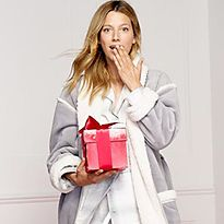 Woman wearing dressing gown with present