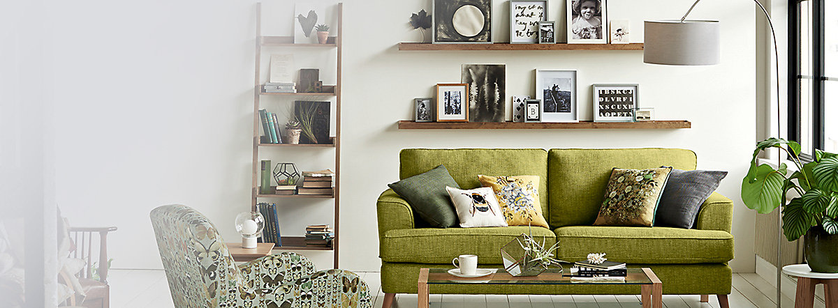 Green sofa with nature print cushions, butterfly print armchair and coffee table in a living room