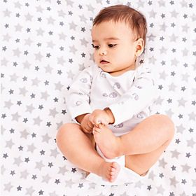 Baby wears white patterned bodysuit