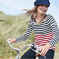 Woman in navy, white and red striped top and a navy baker-boy cap riding a bike