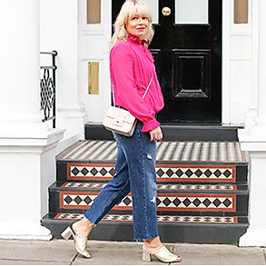 Woman in gold mules and pink jacket