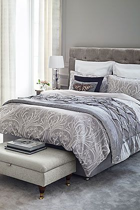 Grey bedding on a divan bed