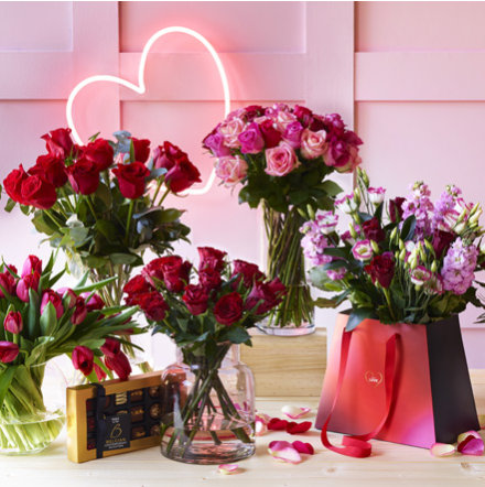 Pink neon 'Say it now' banner and bunches of Valentine's Day flowers