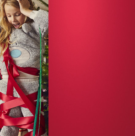 Christmas scene with girl wearing M&S pyjamas tangled up in red ribbon
