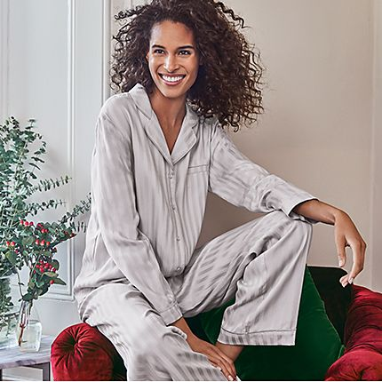 Woman sitting on a red velvet chair wearing silver striped long sleeve pyjamas