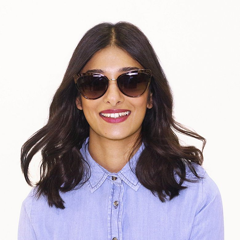 Tejinder wears sunglasses with tortoiseshell-print frames