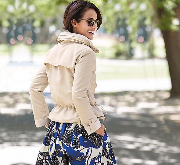 Woman in cream jacket and floral skirt