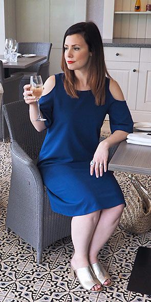 Blogger Morgana wearing a blue dress with cutaway shoulder detail