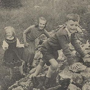 Black and white photo of children playing in rubble