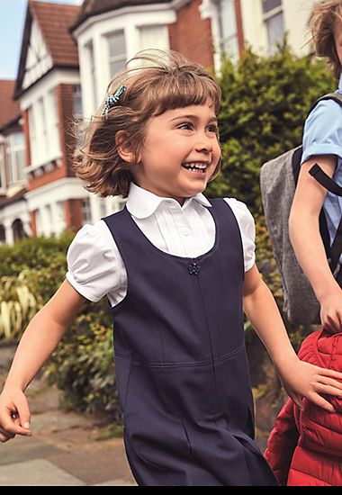 Girl wearing M&S school pinafore and short-sleeved white blouse