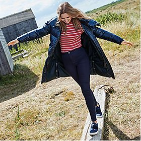 Woman wearing blue padded jacket, striped top, jeans and trainers