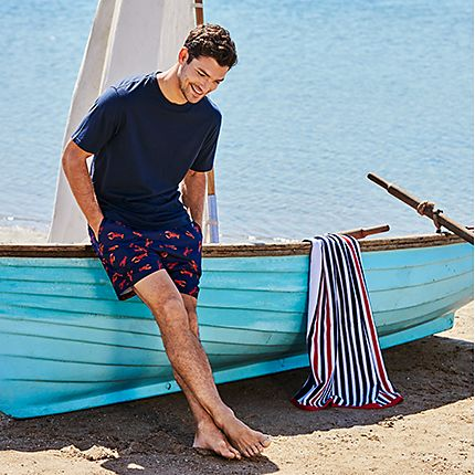 Man modelling swim shorts and T-shirt reclining on a boat