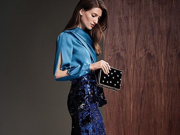 Model wears blue satin blouse, blue sequin pencil skirt and back clutch bag