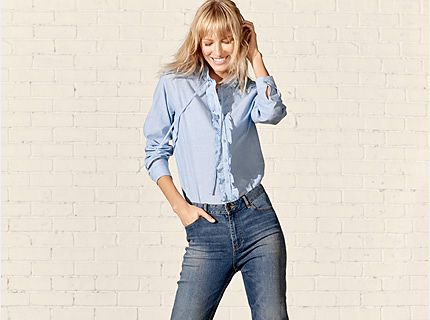 Model wearing jeans and a blue ruffled shirt
