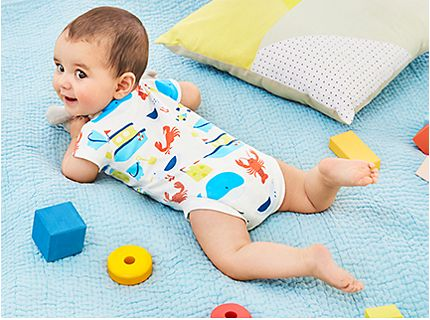 Baby lying on a blanket wearing a printed bodysuit