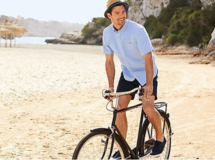 Man wearing mens casual clothes riding a bike