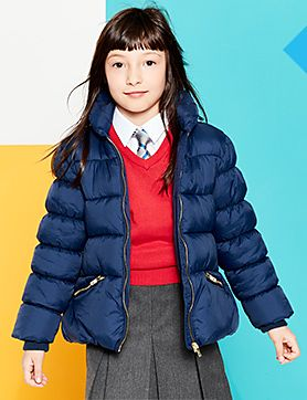 A girl wearing a navy coat and red school jumper