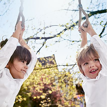 Two children in M&S school shirts hanging from a tree